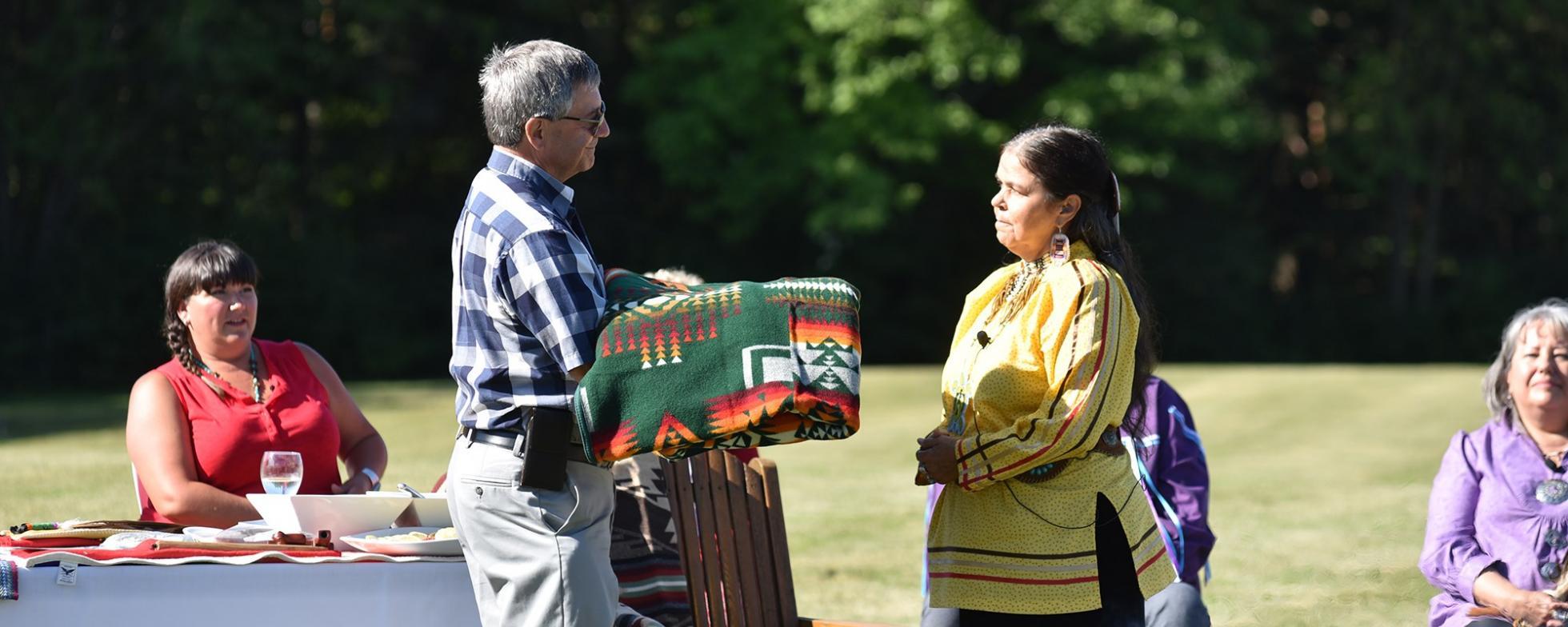 EN: A man is presenting a woman with a patterned blanket FR: Un homme présente une femme avec une couverture à motifs